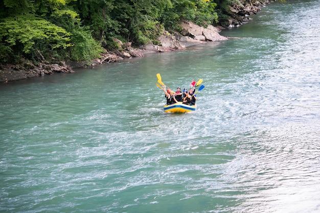 男性と女性のグループが川でラフティング、極端で楽しいスポーツ