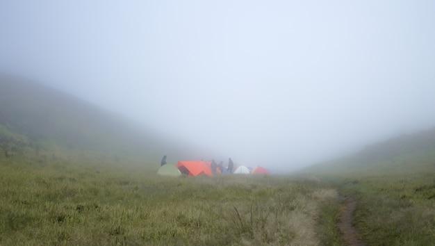 霧の丘の下でテントを張る登山家のグループ
