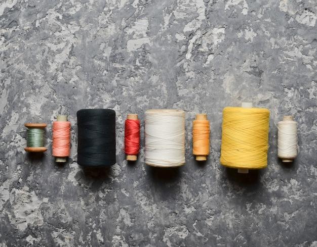 Группа в составе пестротканые пасма потока на серой конкретной предпосылке. концепция рукоделия. сделано ручной пошив одежды.
