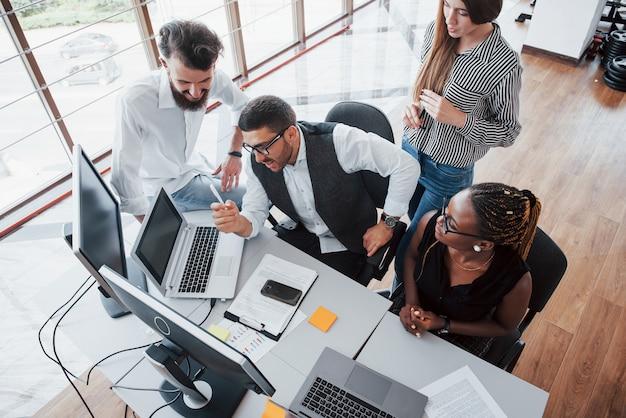 Группа многонациональных занятых людей, работающих в офисе.