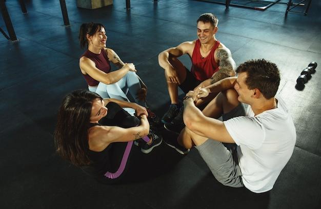 체육관에서 운동을 하는 근육질 운동선수 그룹. 체조, 훈련, 피트니스 운동 유연성. 활동적이고 건강한 생활 방식, 청소년, 보디 빌딩. 크런치 또는 복근 훈련, 평면도.