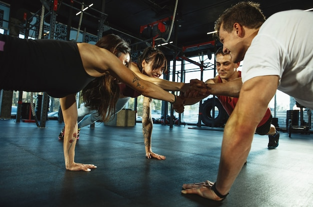 체육관에서 운동을 하는 근육질 운동선수 그룹. 체조, 훈련, 피트니스 운동 유연성. 활동적이고 건강한 생활 방식, 청소년, 보디 빌딩. 스트레칭과 플랭크 훈련.