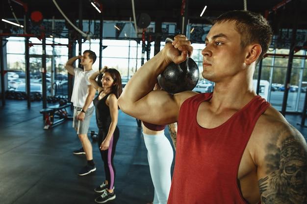 체육관에서 운동을 하는 근육질 운동선수 그룹. 체조, 훈련, 피트니스 운동 유연성. 활동적이고 건강한 생활 방식, 청소년, 보디 빌딩. 웨이트 트레이닝, 스쿼트.