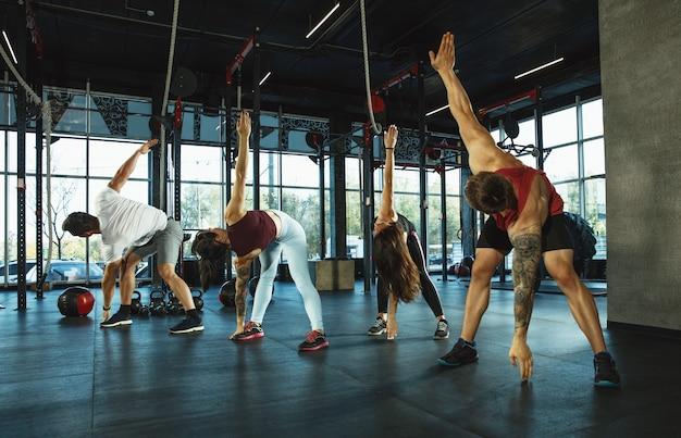 Группа мускулистых спортсменов, тренирующихся в тренажерном зале, гимнастика, тренировка, фитнес