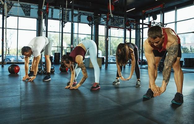 ジムでトレーニングをしている筋肉アスリートのグループ体操トレーニングフィットネス