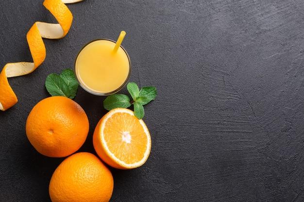 暗いテーブルの上のオレンジのグループとジュースのグラス