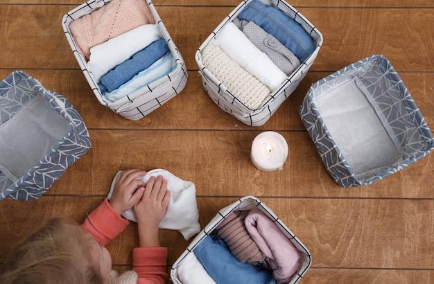 흰색 바구니에 접을 준비가 된 오가닉 코튼 의류 그룹. 옷장 조직의 개념.