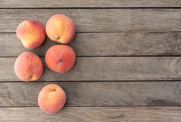 コピースペースのある木製のテーブルの上の桃のグループ。