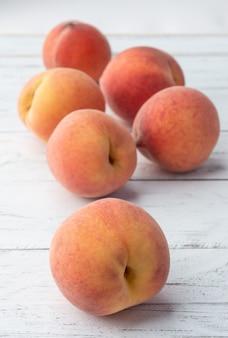 木製のテーブルの上の桃のグループ。