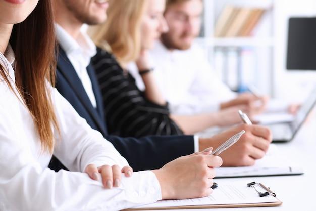 Группа людей на семинаре делает записи в блокноте ручкой