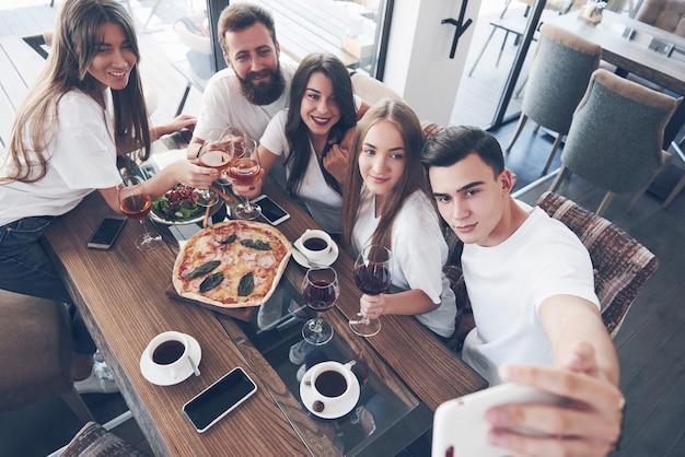 Группа людей делает селфи в кафе. лучшие друзья собрались за обеденным столом, ели пиццу и распевали разные напитки.