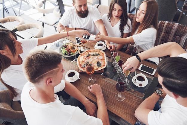 한 무리의 사람들이 카페에서 셀카 사진을 찍습니다. 가장 친한 친구들이 저녁 식사 테이블에 모여 피자를 먹고 다양한 음료를 불렀습니다.