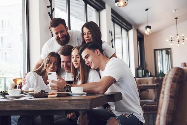 人々のグループがカフェで自分撮り写真を作ります。親友たちは、ピザを食べたり、さまざまな飲み物を歌ったりして、夕食の席に集まりました。