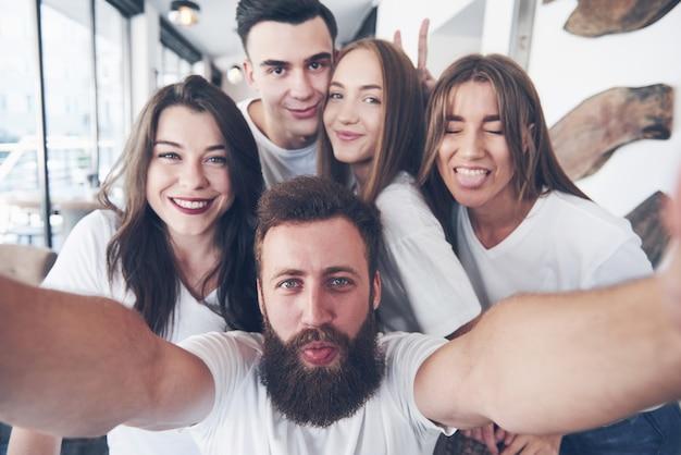 人々のグループがカフェで自分撮り写真を作ります。親友が集まった
