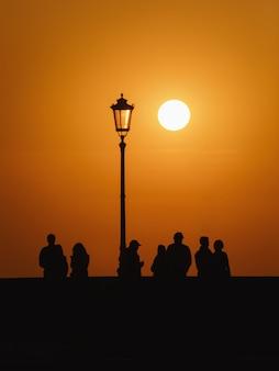 Группа людей на тротуаре стоит на фоне закатного неба и солнца, уличный фонарь