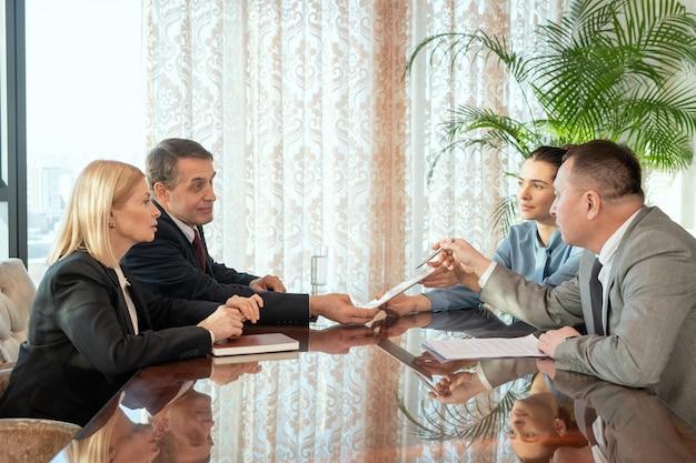 Группа людей, сидящих за столом и обсуждающих