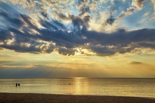 人々のグループは、素晴らしい空を背景に日没時に暖かい海で泳ぎます