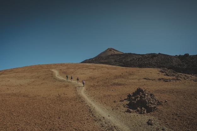 山に向かって登る小道を歩く人々のグループ