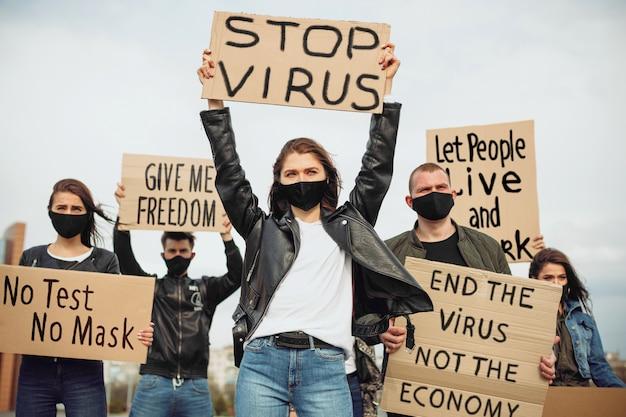 ポスターとの会議に抗議するマスクとポスターを持つ人々のグループがウイルスの偽物を阻止