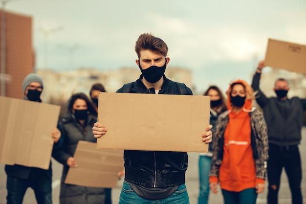 抗議するマスクとポスターを持つ人々のグループコロナウイルスに対するそして検疫の導入に対する住民の抗議