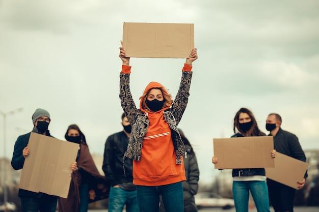 抗議するマスクとポスターを持つ人々のグループコロナウイルスに対する住民の抗議