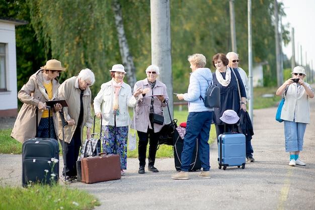 Группа позитивных пожилых людей пожилого возраста, путешествующих с помощью планшетов в ожидании поезда перед поездкой