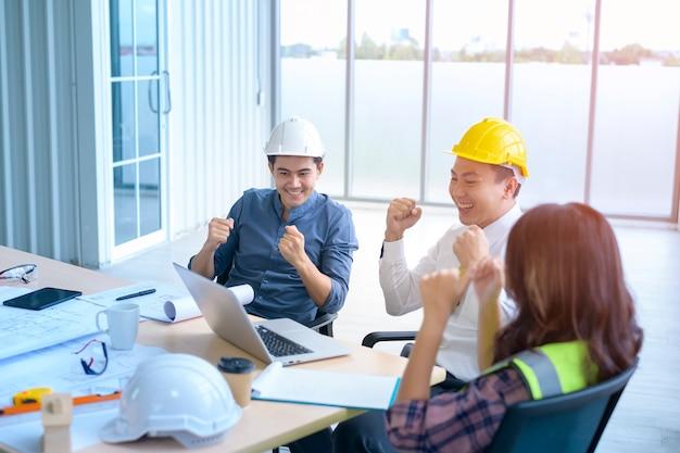 Группа профессиональных инженеров, встречающихся и празднующих успешный проект в современном офисе, совместной работы и запуска бизнес-концепции.