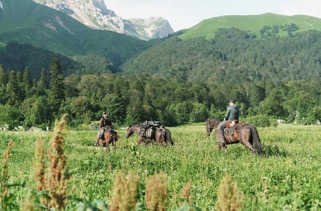 산봉우리를 배경으로 들판에서 말을 타고 있는 라이더 그룹.