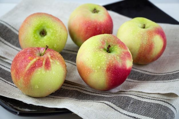 Группа спелых красных и желтых яблок.