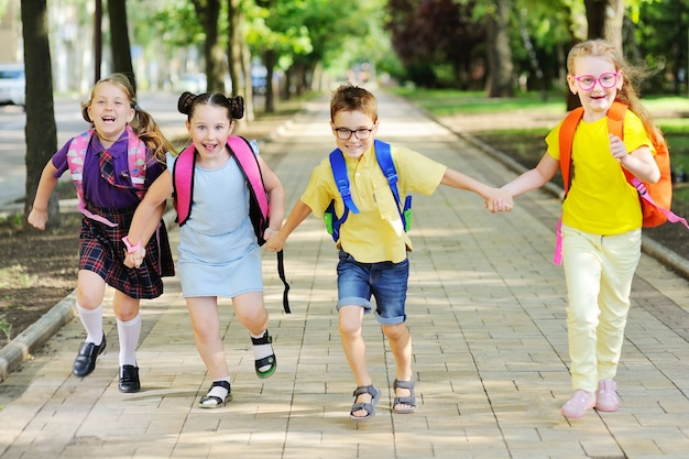 Группа школьников в цветных одеждах со школьными рюкзаками и рюкзаками бежит в школу, улыбаясь. учебный год, снова в школу, день знаний.