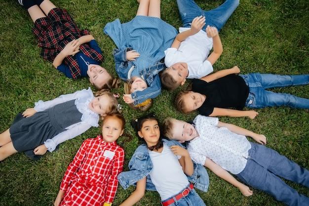 Группа школьников лежат на траве в кругу и веселятся