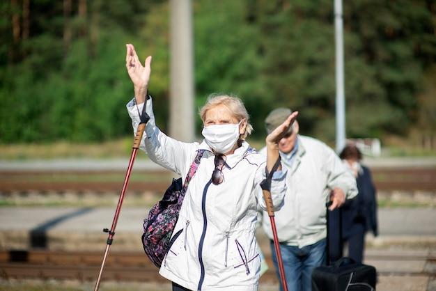 Группа пожилых путешественников с масками на лицах пересекает железнодорожные пути.