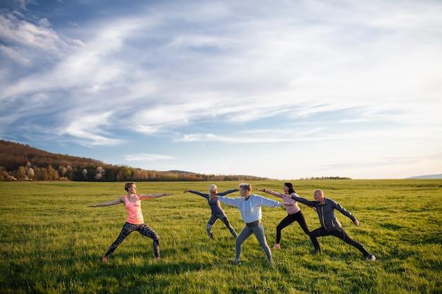 自然の中で屋外で運動をしているスポーツインストラクターとアクティブなライフスタイルを持つ高齢者のグループ。