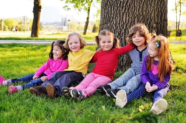 Группа маленьких детей в яркой одежде, сидящих на траве под деревом в парке, смеясь и улыбаясь.