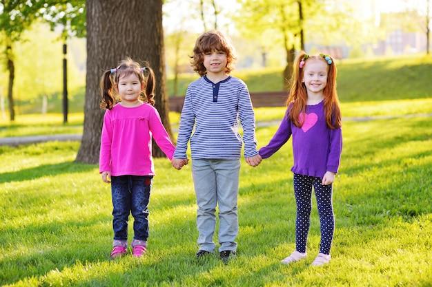 손을 잡고 웃 고 작은 어린이들의 그룹 잔디, 나무와 공원.