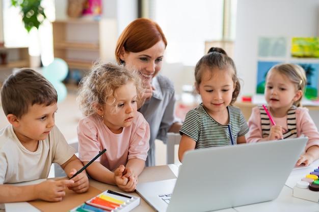 랩톱을 사용하여 교실 실내 바닥에 교사와 함께 작은 보육원 어린이 그룹.