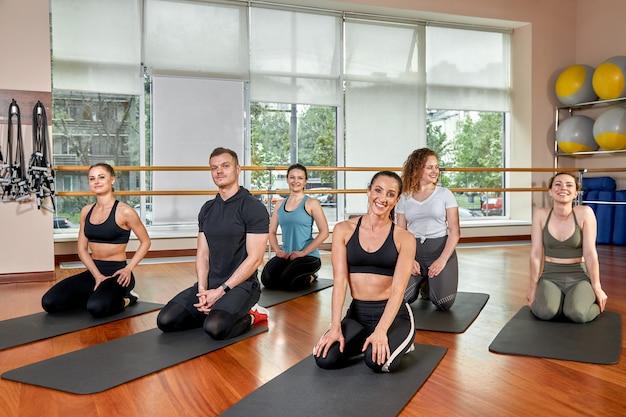 Группа спортивных молодых людей в спортивной одежде, в тренажерном зале, отжимания или доски в тренажерном зале. групповая концепция фитнеса, групповые тренировки, мотивация