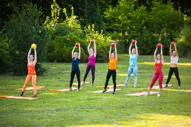 Группа спортивных девушек, которые тренируются с фитнес-мячами в парке. силовая тренировка на открытом воздухе