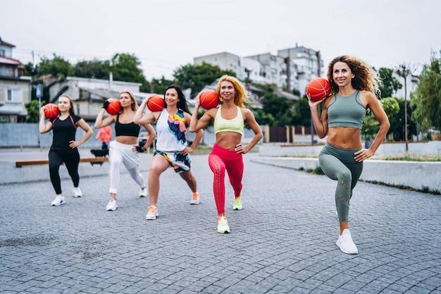 スポーティな女性のグループがポーズを取り、水の近くの通りでオレンジ色のボールでエクササイズを行います。アクティブなライフスタイル