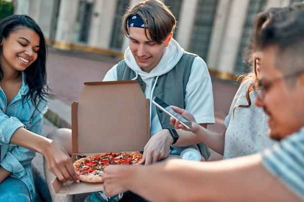 学生のグループがキャンパスの外の階段に座って、ピザとソーダを食べます。友達のグループがリラックスしてチャットしたり、スマートフォンで写真を撮ったりしています。