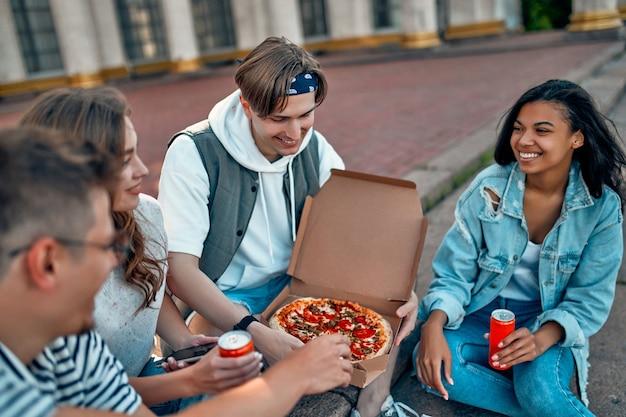 Группа студентов сидит на ступеньках за пределами кампуса и ест пиццу с содовой. группа друзей отдыхает и болтает.