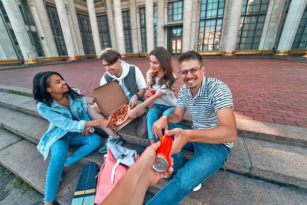 学生のグループがキャンパスの外の階段に座って、ピザとソーダを食べます。友達のグループがリラックスしておしゃべりしています。