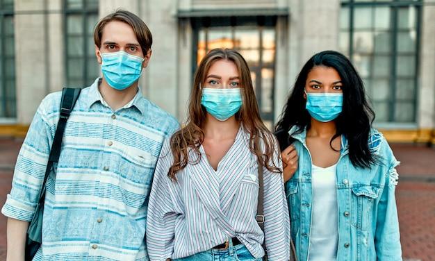 キャンパスの近くで防護マスクを着用している学生のグループ。