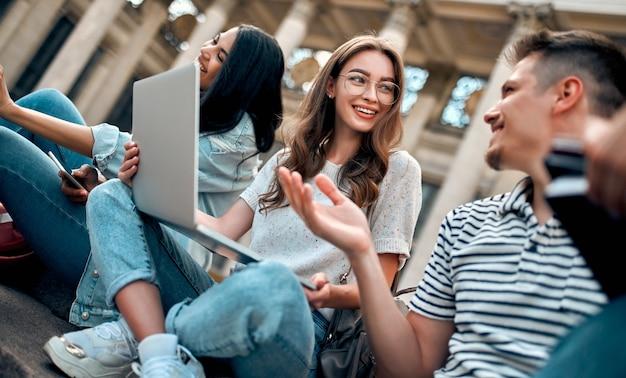 Группа студентов с ноутбуками сидят на ступеньках возле кампуса и общаются.