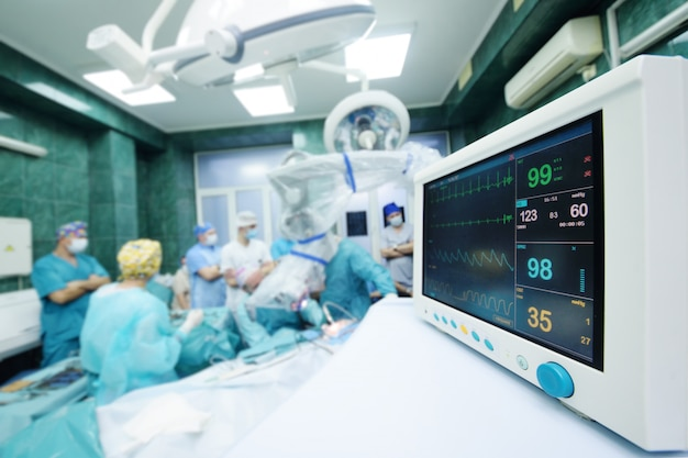 外科医のグループは、患者の生命機能モニターのクローズアップを操作します。