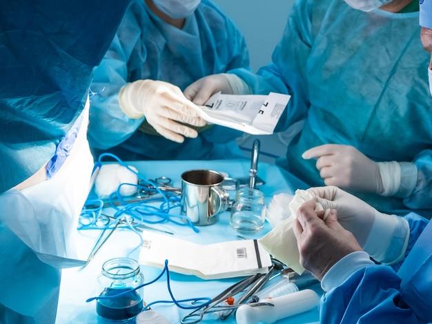 수술 도구를 사용하여 환자의 항문에 최소 침습 수술을 수행하는 외과의사 그룹. 외과의사는 살균된 파란색 수술복을 입고 있습니다.