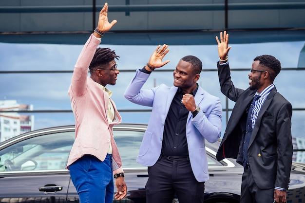 Группа из трех успешных афро-американских бизнесменов в стильном костюме разговаривает и радуется на фоне окна небоскреба. работа в команде и концепция успеха.