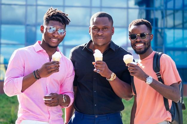 Группа из трех афроамериканцев ест мороженое в вафельном рожке летом в парке