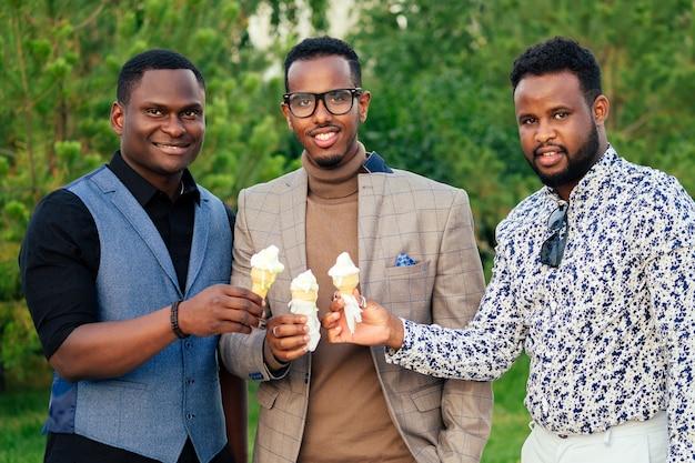 Группа из трех черных мужчин в стильных костюмах на встречу в летнем парке. афро-американцы друзья латиноамериканского бизнесмена едят ванильное белое сладкое мороженое на пикнике вафельного рога на открытом воздухе.