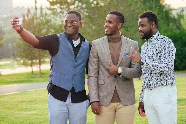 夏の公園でスタイリッシュなスーツを着た3人の黒人男性のグループ。アフリカ系アメリカ人の友人のヒスパニック系ビジネスマンが屋外の電話で自分撮りを撮影しました
